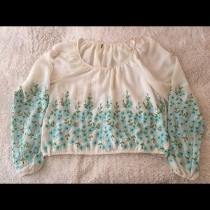 Free people shirt with embroidered blue flowers.